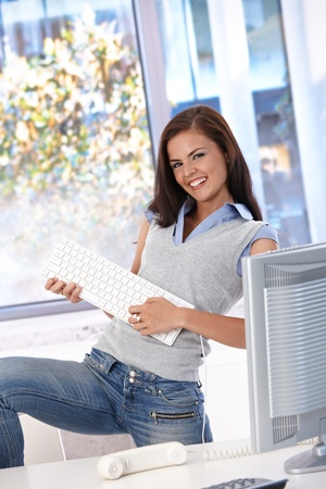 Joyous office worker girl playing guitar on keyboard, having fun in bright office. photo