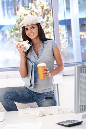 Casual girl having lunch in office, smiling, looking at camera. photo