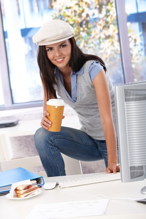 Casual girl having coffee-break at desk, smiling, looking at camera. photo