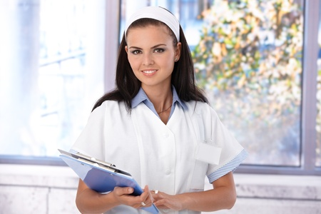 Portrait of attractive young nurse standing at hospital corridor, smiling. Stock Photo - 9868419
