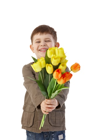 bouquet flowers: Little boy giving flowers to someone, smiling happily. Stock Photo