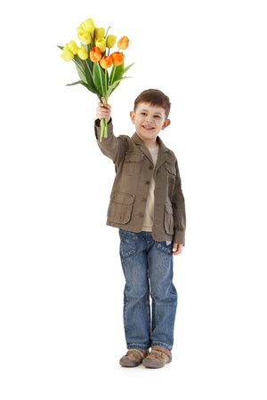 only boys: Cute little 5 year old kid holding a bouquet of tulips, smiling.