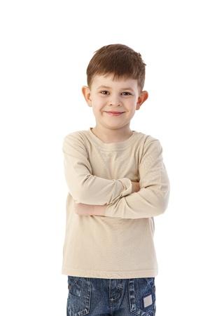 crossed: Cute little boy standing arms crossed, smiling, looking at camera.