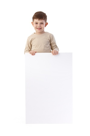 Little boy holding a blank sheet, smiling, looking at camera. photo