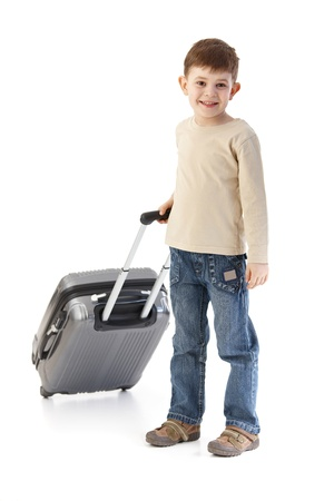 Little boy traveling with suitcase, smiling. photo