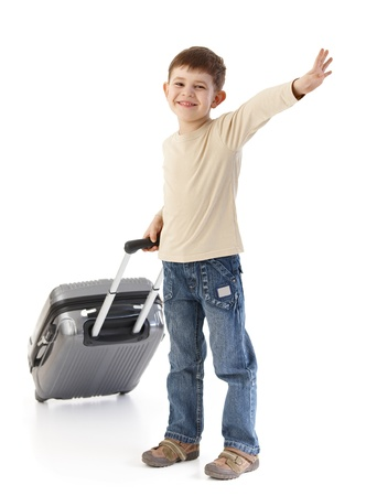 Happy kid traveling with suitcase, waving, smiling. photo