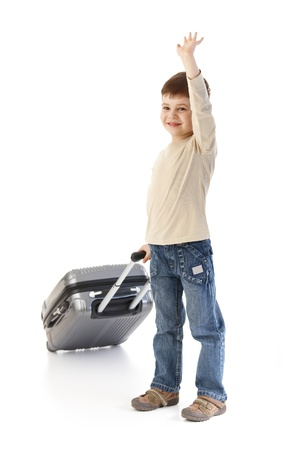 Cute little kid holding baggage waving, smiling. photo