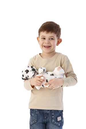 Sweet little boy holding dog in hands, smiling happily. photo