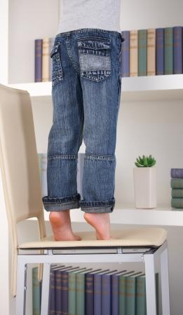 Little tiptoing kid in cima alla sedia per raggiungere qualcosa sul scaffale.