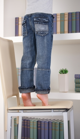 Little kid tiptoing on top of chair to reach something on bookshelf. photo