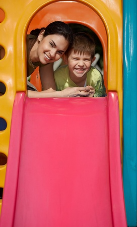 Mother and son at top of slide at playground, smiling, looking at camera photo