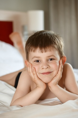 6 years: Little boy laying on front on bed, looking at camera Stock Photo