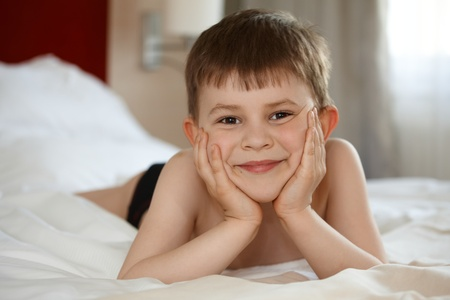 stockphoto: Cute little kid laying on bed, smiling, looking at camera