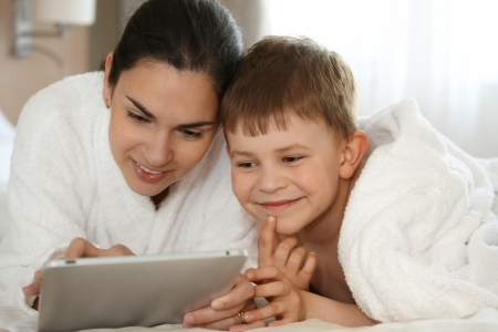 woman bathrobe: Mother and son playing on tablet, smiling, laying on bed.