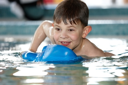 Cute little kid playing at swimming pool, smiling, having fun photo