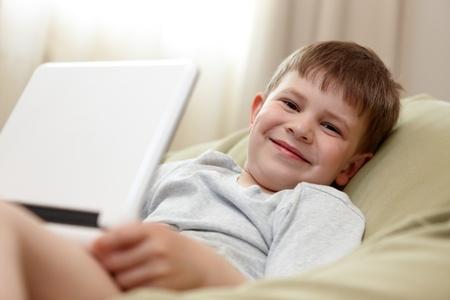 Cute kid using laptop computer, smiling, looking at camera photo