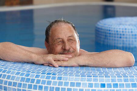 Elderly man relaxing in spa, smiling, looking away. photo