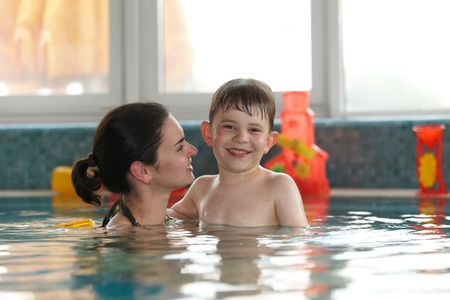Happy kid and mother embracing in swimming pool, smiling. photo