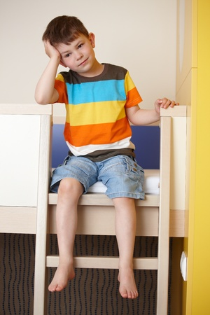 Sleepy little boy sitting on bunk bed.
