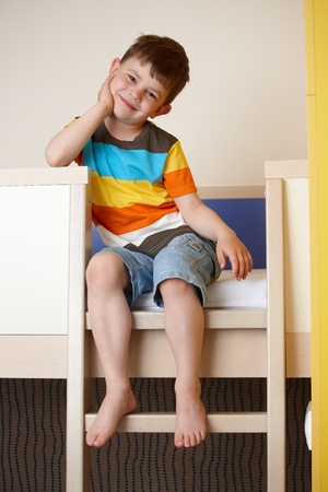 only boys: Happy little kid sitting on bunk bed, smiling.