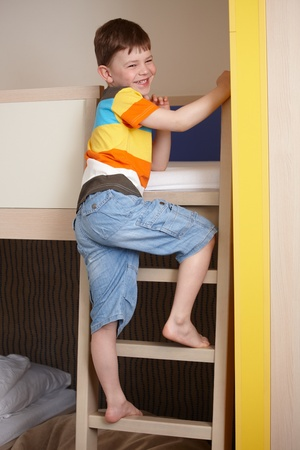 Smiling little boy going up the ladder of bunk bed. photo