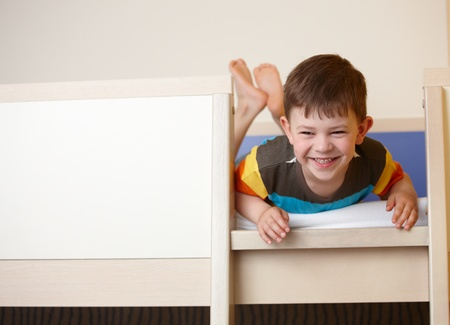 lying in front: Little kid laughing on top of bunk bed, laying on front.