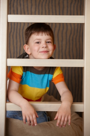 Little boy playing behind ladder, smiling, looking at camera. photo