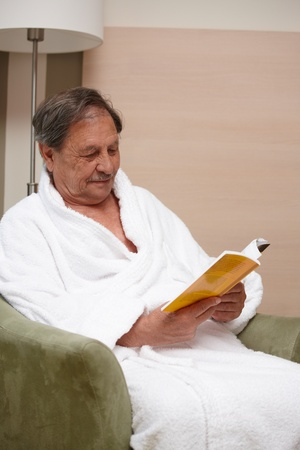 Old man relaxing in armchair, reading a book. photo