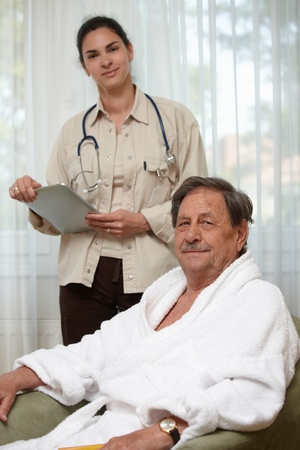 consultant physicians: Elderly man waiting for examination, young female doctor at background.