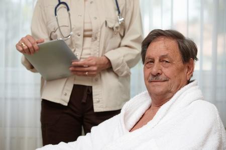 bathrobes: Mature man at health control, looking at camera.