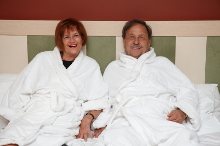 Happy mature couple laying on bed at wellness hotel, smiling, looking at camera. photo