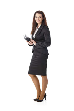 Smiling elegant pretty businesswoman standing with personal calendar handheld, looking at camera. photo