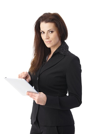 Portrait of businesswoman using touchscreen tablet computer, looking at camera. photo
