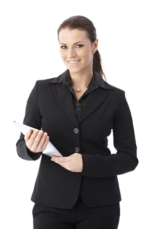 one mid adult woman only: Businesswoman standing with touchscreen computer handheld, smiling at camera, studio portrait.