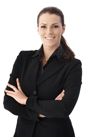 Cheerful businesswoman standing with arms folded, smiling at camera.