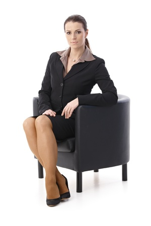 Portrait of determined businesswoman sitting in armchair, looking at camera, isolated on white.