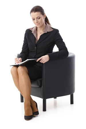 tomando: Smiling businesswoman taking notes into personal calendar, sitting in armchair, isolated on white.