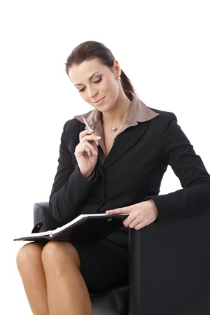 Businesswoman thinking looking at personal organizer with pen handheld, smiling, sitting in armchair. photo