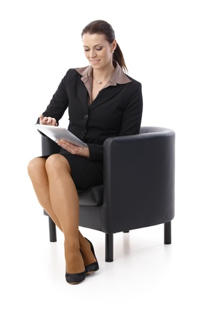 Businesswoman sitting in armchair using touchscreen computer, smiling, photo
