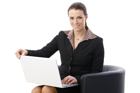 Businesswoman sitting in armchair with laptop computer, smiling at camera, isolated on white. Stock Photo - 9868508