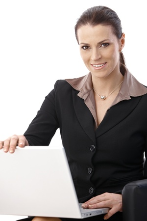 Cheerful businesswoman in armchair opening laptop computer, smiling at camera. photo