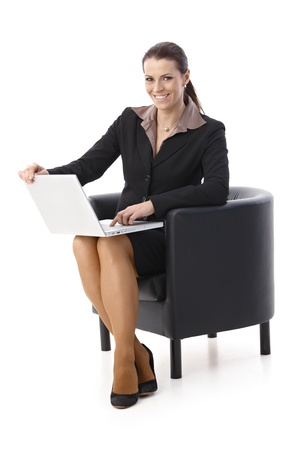 Laughing businesswoman with laptop computer, sitting in armchair, looking at camera, isolated on white. photo