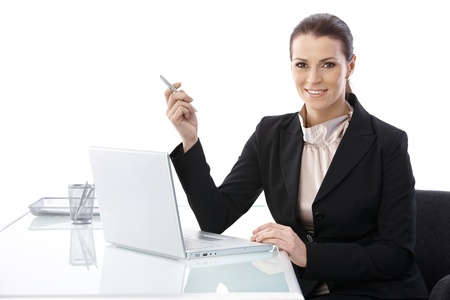Mid-adult elegant businesswoman sitting at desk, using laptop computer holding pen, smiling at camera. photo