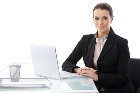 looking good: Cutout portrait of businesswoman sitting at desk with laptop computer, smiling at camera. Stock Photo