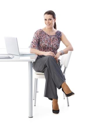 カメラは、完全な長さの画像で笑って、机に座って幸せな office アシスタントの肖像画は、白で隔離されます。