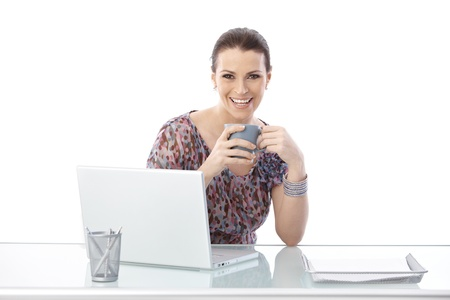 Laughing woman sitting at office desk with laptop computer, holding coffee mug, looking at camera, isolated on white. photo