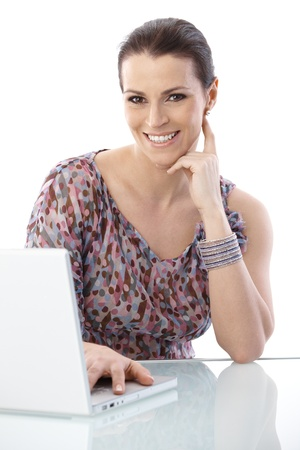 Portrait of laughing woman working on laptop, looking at camera. Stock Photo - 9868439