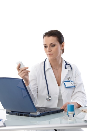 Portrait of female doctor sitting at desk at work, using laptop computer and mobile phone, smiling. Stock Photo - 9868512