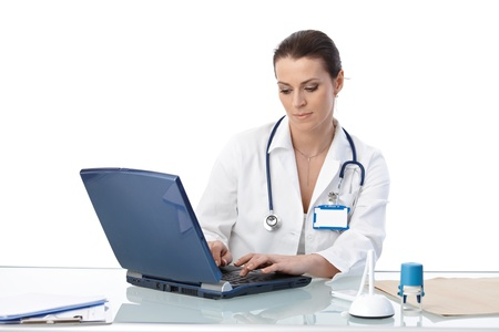 doctor computer: General practitioner sitting at desk, typing on laptop computer, isolated on white. Stock Photo