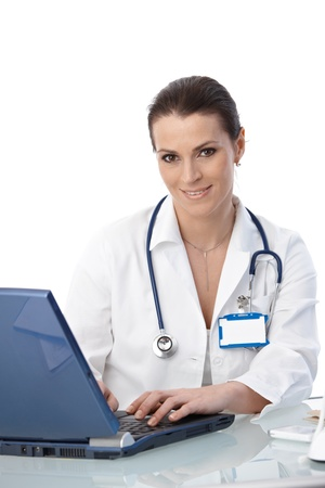 medical physician: Portrait of smiling doctor working on laptop computer at desk, looking at camera. Stock Photo